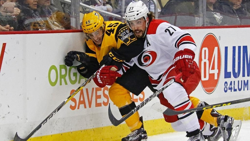 "FILE - In this Sunday, April 2, 2017, file photo, Carolina Hurricanes' Justin Faulk (27) checks Pittsburgh Penguins' Josh Archibald (45) into the boards during the second period of an NHL hockey game in Pittsburgh. Players' anger over the NHL's decision not to go to the 2018 Olympics could foreshadow another ugly labor fight in a few years. The league offered an agreement to go to Pyeongchang next year in exchange for extending the CBA until 2025, but players rejected what Faulk likened to a ""ridiculous"" bad trade. (AP Photo/Gene J. Puskar, File)"
