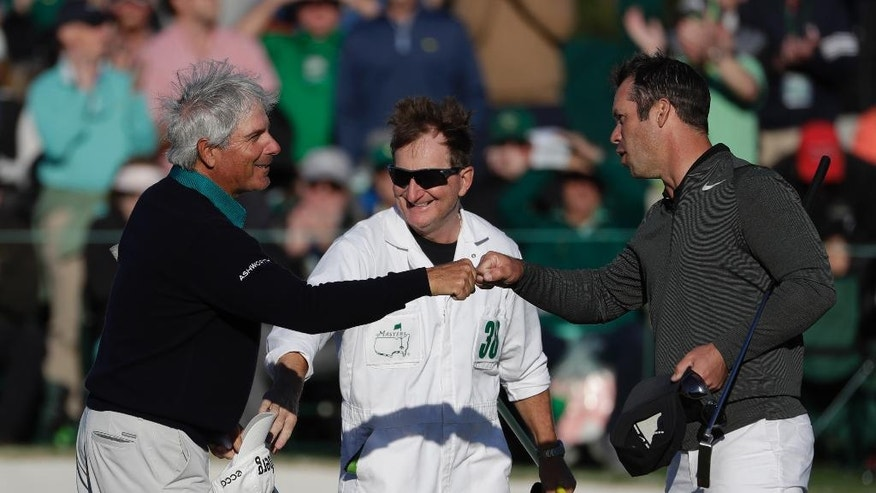 Fred Couples fist bumps Paul Casey of England, on the 18th green during the second round of the Masters golf tournament Friday, April 7, 2017, in Augusta, Ga. (AP Photo/Matt Slocum)