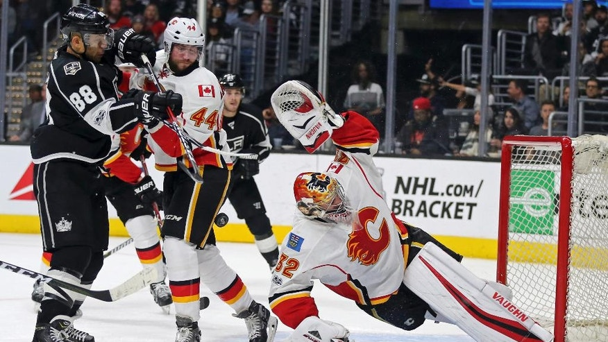 Calgary Flames goalie Jon Gillies (32) stretches to protect the goal, with defenseman Matt Bartkowski (44) and Los Angeles Kings right winger Jarome Iginia (88) in the mix during the second period of an NHL hockey game in Los Angeles on Thursday, April 6, 2017. (AP Photo/Reed Saxon)