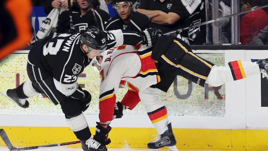 Calgary Flames defenseman Dougie Hamilton (27) and Los Angeles Kings right winger Dustin Brown (23) tangle during the second period of an NHL hockey game in Los Angeles on Thursday, April 6, 2017. (AP Photo/Reed Saxon)
