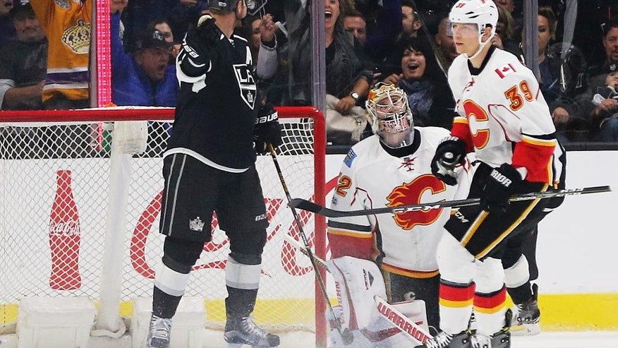 Calgary Flames goalie Jon Gillies (32) and right winger Alex Chiasson (39) react as Los Angeles Kings center Jeff Carter (77) celebrates a goal during the first period of an NHL hockey game in Los Angeles on Thursday, April 6, 2017. (AP Photo/Reed Saxon)