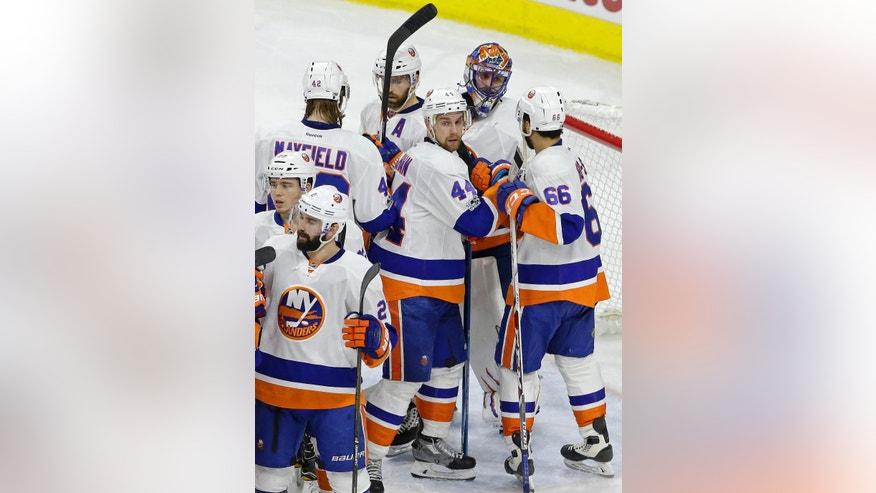 New York Islanders goalie Jaroslav Halak, of Slovakia, is congratulated by teammates following the Islanders 3-0 win over the Carolina Hurricanes in an NHL hockey game in Raleigh, N.C., Thursday, April 6, 2017. (AP Photo/Gerry Broome)