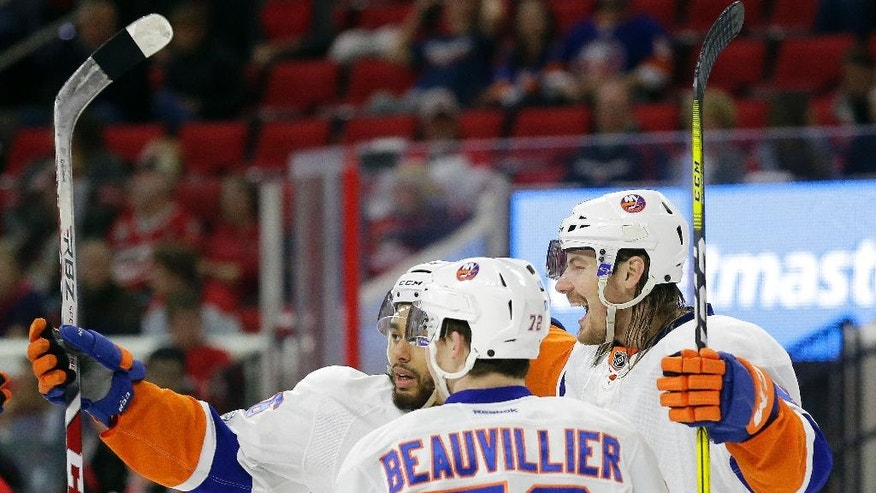 New York Islanders' Scott Mayfield, right, reacts with Anthony Beauvillier (72) and Joshua Ho-Sang following Mayfield's goal against the Carolina Hurricanes during the first period of an NHL hockey game in Raleigh, N.C., Thursday, April 6, 2017. (AP Photo/Gerry Broome)