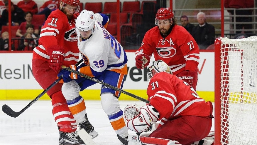 New York Islanders' Brock Nelson (29) shoots and scores while Carolina Hurricanes goalie Eddie Lack (31), of Sweden, Jordan Staal (11) and Justin Faulk (27) defend during the first period of an NHL hockey game in Raleigh, N.C., Thursday, April 6, 2017. (AP Photo/Gerry Broome)