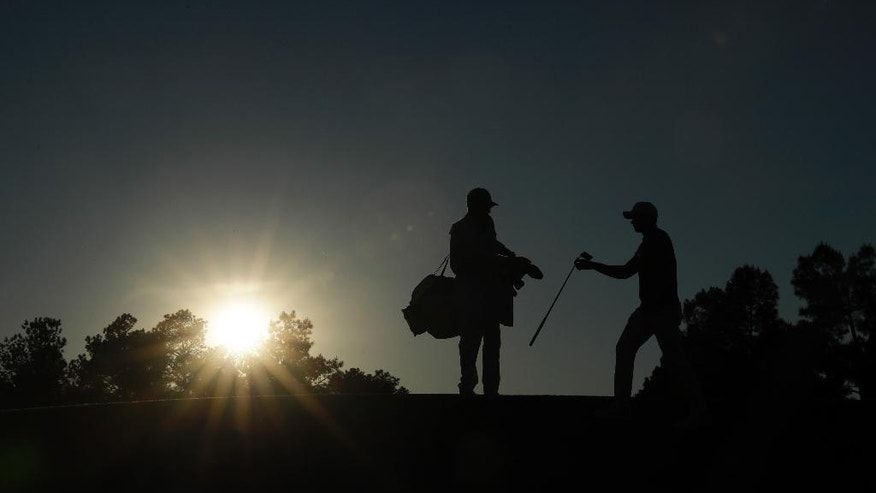 Jason Day or Australia, gives his club to his caddie Colin Swatton on the 17th hole during the second round of the Masters golf tournament Friday, April 7, 2017, in Augusta, Ga. (AP Photo/David J. Phillip)