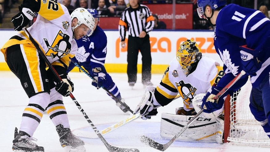 Toronto Maple Leafs center Zach Hyman (11) and Pittsburgh Penguins defenseman Mark Streit (32) vie for control of the puck as Penguins goalie Marc-Andre Fleury (29) watches during the second period of an NHL hockey game in Toronto on Saturday, April 8, 2017. (Frank Gunn/The Canadian Press via AP)