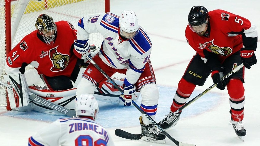 Ottawa Senators' Cody Ceci (5) battles for the puck with New York Rangers' Chris Krieder (20) as Senators goaltender Craig Anderson (41) looks on during the second period of an NHL hockey game in Ottawa on Saturday April 8, 2017.  (Fred Chartrand/The Canadian Press via AP)