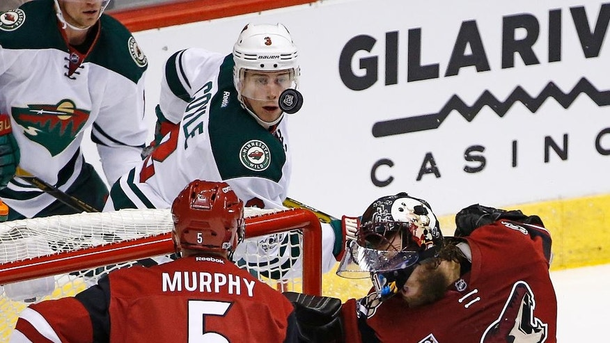 Arizona Coyotes' Mike Smith, right, takes a puck off the face mask as Minnesota Wild's Charlie Coyle (3) and Coyotes' Connor Murphy (5) look on during the first period of an NHL hockey game Saturday, April 8, 2017, in Glendale, Ariz. (AP Photo/Ross D. Franklin)