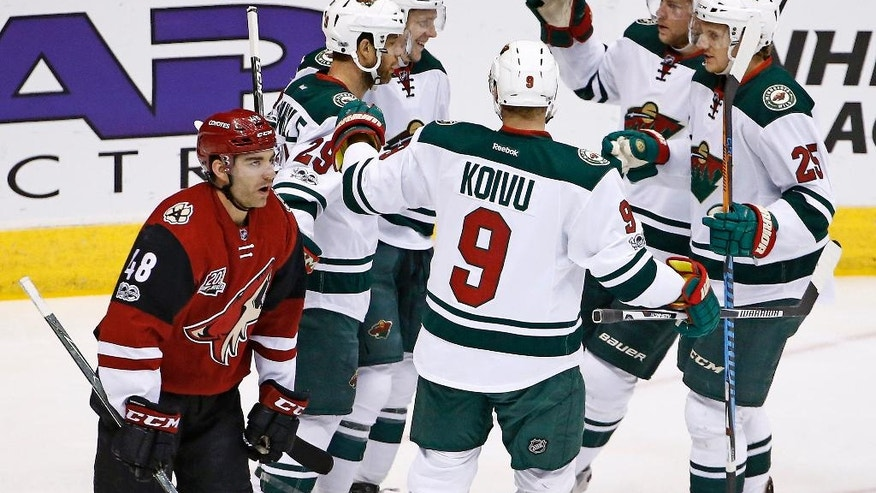 Minnesota Wild's Erik Haula celebrates his goal against the Arizona Coyotes with Jason Pominville (29), Mikko Koivu (9), Jonas Brodin (25) and Christian Folin (5) as Coyotes' Jordan Martinook (48) skates past during the first period of an NHL hockey game Saturday, April 8, 2017, in Glendale, Ariz. (AP Photo/Ross D. Franklin)