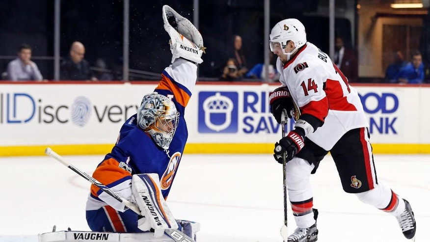New York Islanders goalie Thomas Greiss (1) makes a glove save in front of Ottawa Senators left wing Alexandre Burrows (14) in the first period of an NHL hockey game, Sunday, April 9, 2017, in New York. (AP Photo/Adam Hunger)