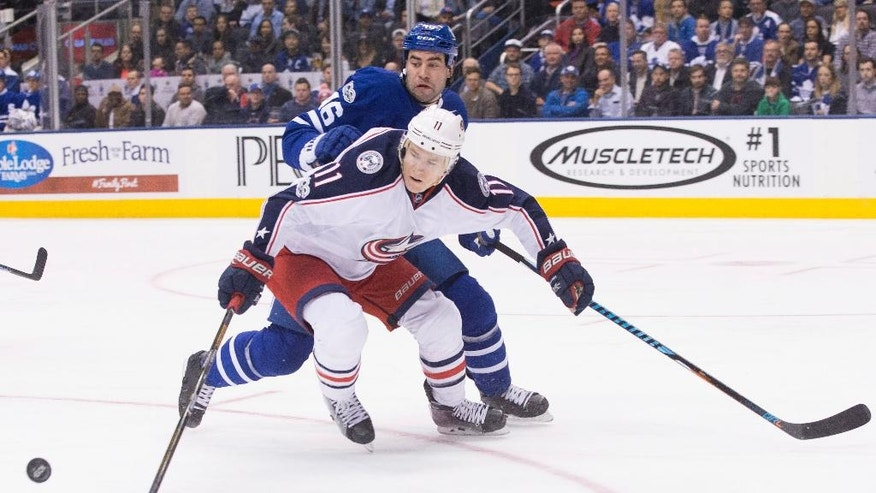 Toronto Maple Leafs' Roman Polak, rear, battles for the puck with Columbus Blue Jackets' Matt Calvert during first period NHL hockey action in Toronto, on Sunday April 9, 2017. (Chris Young/The Canadian Press via AP)