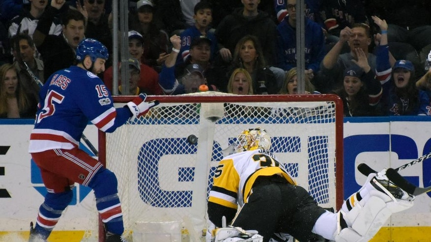 Pittsburgh Penguins goalie Tristan Jarry (35) eyes the puck before gloving the puck as New York Rangers left wing Tanner Glass (15) looks on during the first period of an NHL hockey game Sunday, April 9, 2017, at Madison Square Garden in New York. (AP Photo/Bill Kostroun)