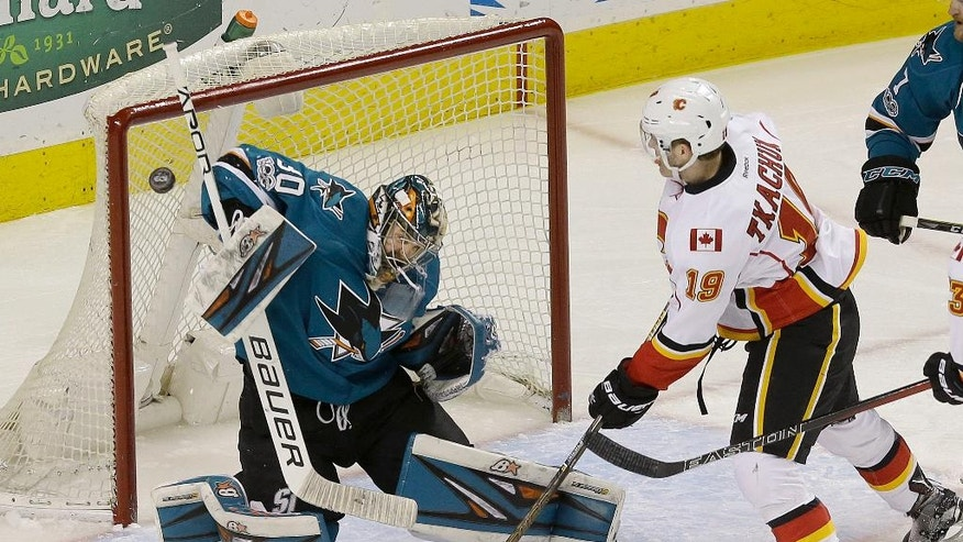 San Jose Sharks goalie Aaron Dell (30) defends a shot next to Calgary Flames left wing Matthew Tkachuk (19) during the first period of an NHL hockey game in San Jose, Calif., Saturday, April 8, 2017. (AP Photo/Jeff Chiu)