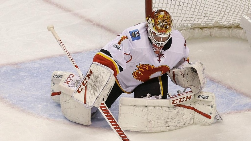 Calgary Flames goalie Brian Elliott (1) deflects a shot against the San Jose Sharks during the first period of an NHL hockey game in San Jose, Calif., Saturday, April 8, 2017. (AP Photo/Jeff Chiu)