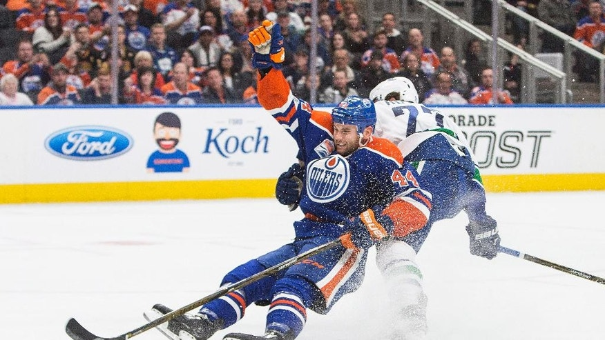 Vancouver Canucks' Ben Hutton (27) takes out Edmonton Oilers' Zack Kassian (44) during second period NHL hockey action in Edmonton, Alberta, Sunday April 9, 2017. (Amber Bracken/The Canadian Press via AP)