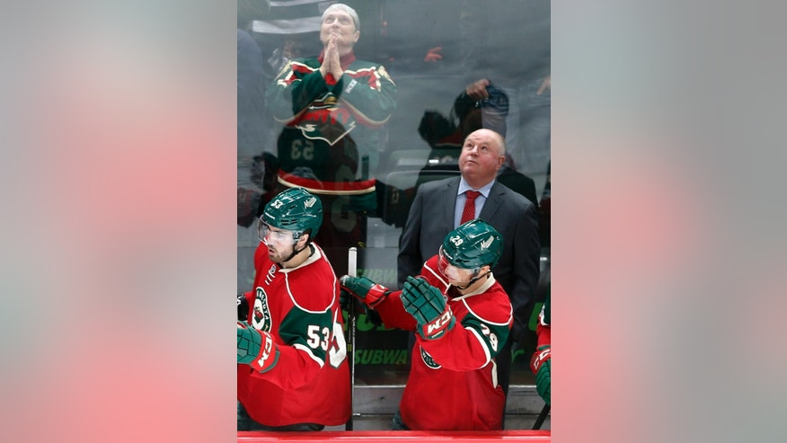 FILE - In this Feb. 18, 2017, file photo, Minnesota Wild head coach Bruce Boudreau watches the replay of a goal by Minnesota Wild's Mikko Koivu, of Finland, during the third period of an NHL hockey game in St. Paul, Minn. Boudreau is back in the playoffs with a third team, the Minnesota Wild in his debut season. For the eighth time in this unique character of a coach's nine postseason appearances, his team has one of the top two records in its conference. But that 1-7 career Game 7 record can't be ignored. (AP Photo/Jim Mone, File)