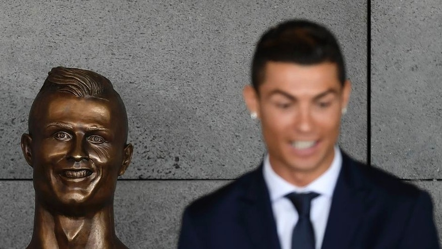 "Portuguese footballer Cristiano Ronaldo stands beside a bust presented during a ceremony to rename Madeira's airport in Funchal as ""Cristiano Ronaldo"", on Madeira island, on March 29, 2017. Airport of Madeira, the birthplace of Portuguese footballer Cristiano Ronaldo, was renamed today in honor of the quadruple Ballon d'or and captain of the Portuguese team sacred European champion last summer. / AFP PHOTO / FRANCISCO LEONG (Photo credit should read FRANCISCO LEONG/AFP/Getty Images)"