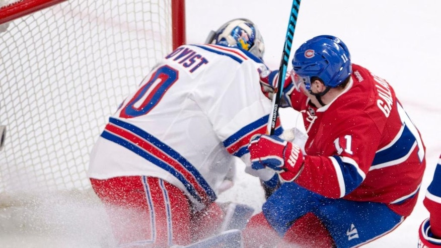 Montreal Canadiens right wing Brendan Gallagher (11) slides into New York Rangers goalie Henrik Lundqvist (30) during the first period of Game 1 of an NHL first-round hockey playoff series Wednesday, April 12, 2017, in Montreal. (Ryan Remiorz/The Canadian Press via AP)