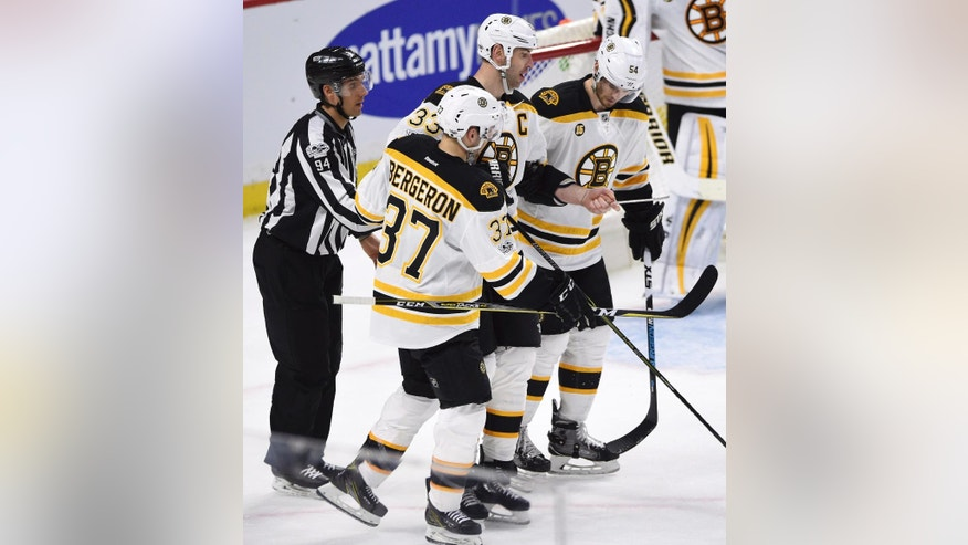 Boston Bruins' defenseman Zdeno Chara, center, is given a hand off the ice after losing a skate blade during second period of game one NHL Stanley Cup hockey playoff action against the Ottawa Senators, in Ottawa, Wednesday, April 12, 2017. (Sean Kilpatrick/The Canadian Press via AP)
