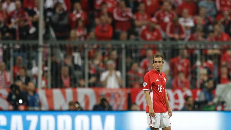 Bayern's Philipp Lahm looks at Real Madrid's Cristiano Ronaldo celebrating with teammates scoring his side's 2nd goal during the Champions League quarterfinal first leg soccer match between FC Bayern Munich and Real Madrid, in Munich, Germany, Wednesday, April 12, 2017. (AP Photo/Matthias Schrader)