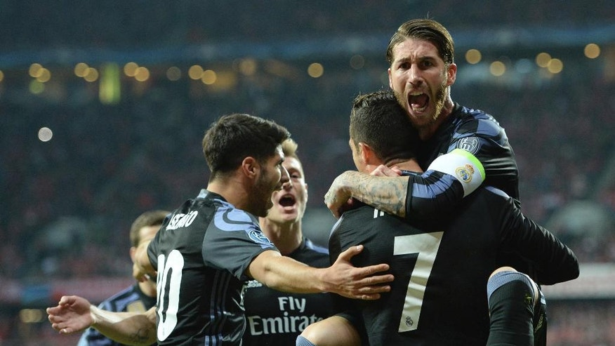 Real Madrid's Sergio Ramos, right, jumps on his teammate and scorer Cristiano Ronaldo to celebrate their side's 2nd goal during the Champions League quarterfinal first leg soccer match between FC Bayern Munich and Real Madrid, in Munich, Germany, Wednesday, April 12, 2017. (Andreas Gebert/dpa via AP)