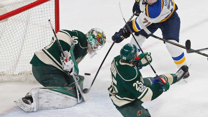 Minnesota Wild goalie Devan Dubnyk, left, stops a shot by St. Louis Blues' Vladimir Sobotk, right, of the Czech Republic during the first period of Game 1 of an NHL hockey first-round playoff series Wednesday, April 12, 2017, in St. Paul, Minn. (AP Photo/Jim Mone)