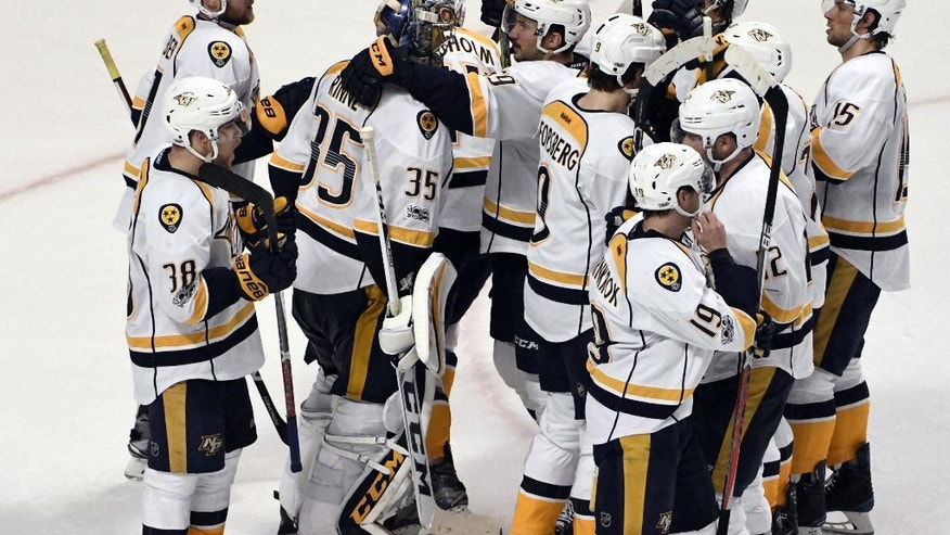 Nashville Predators goalie Pekka Rinne (35) is congratulated by teammates after their win over the Chicago Blackhawks in Game 1 of a first-round NHL hockey playoff series Thursday, April 13, 2017, in Chicago. (AP Photo/David Banks)