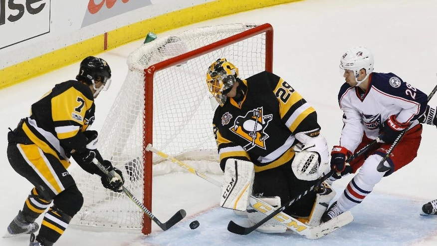 Pittsburgh Penguins' Matt Cullen (7) clears a rebound behind goalie Marc-Andre Fleury (29) before Columbus Blue Jackets' Oliver Bjorkstrand (28) can get his stick on it during the period in Game 2 of an NHL first-round hockey playoff series in Pittsburgh, Friday, April 14, 2017. (AP Photo/Gene J. Puskar)