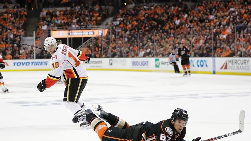 Anaheim Ducks' Rickard Rakell, front, of Sweden, falls to the ice as he moves the puck past Calgary Flames' Matt Stajan during the first period in Game 1 of a first-round NHL hockey Stanley Cup playoff series Thursday, April 13, 2017, in Anaheim, Calif. (AP Photo/Jae C. Hong)