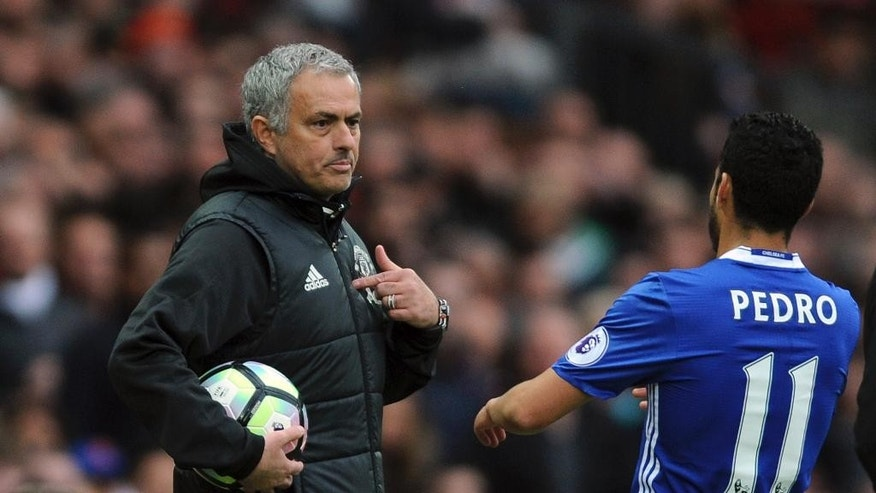 Manchester United's team manager Jose Mourinho, left, talks to Chelsea's Pedro during the English Premier League soccer match between Manchester United and Chelsea at Old Trafford stadium in Manchester, Sunday, April 16, 2017.(AP Photo/ Rui Vieira)