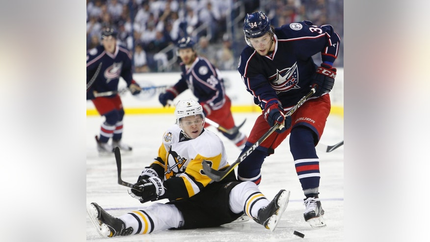 Columbus Blue Jackets' Josh Anderson, right, tries to control the puck as Pittsburgh Penguins' Olli Maatta, of Finland, defends during the second period in Game 3 of a first-round NHL hockey playoff series, Sunday, April 16, 2017, in Columbus, Ohio. (AP Photo/Jay LaPrete)