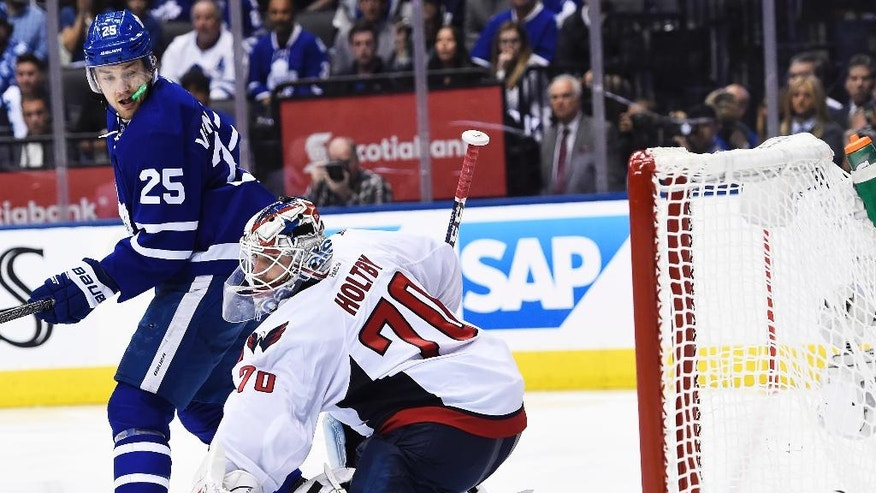 Toronto Maple Leafs left wing James van Riemsdyk (25) watches Tyler Bozak's game-winning goal on Washington Capitals goalie Braden Holtby (70) during overtime in Game 3 of an NHL Stanley Cup first-round playoff series in Toronto on Monday, April 17, 2017. (Nathan Denette/The Canadian Press via AP)