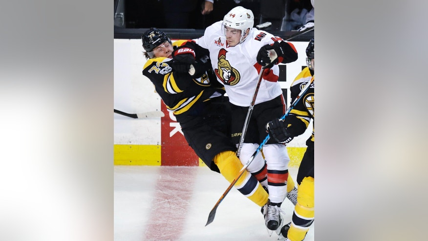 Ottawa Senators center Jean-Gabriel Pageau, right, drops Boston Bruins defenseman Charlie McAvoy to the ice on a hard check during the first period in Game 3 of a first-round NHL hockey playoff series in Boston, Monday, April 17, 2017. (AP Photo/Charles Krupa)