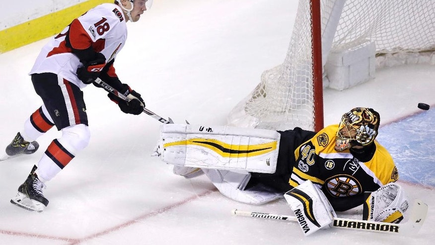 Boston Bruins goalie Tuukka Rask (40) looks up at Ottawa Senators center Ryan Dzingel (18) as the puck flies through the crease during the first period in Game 3 of a first-round NHL hockey playoff series in Boston, Monday, April 17, 2017. (AP Photo/Charles Krupa)