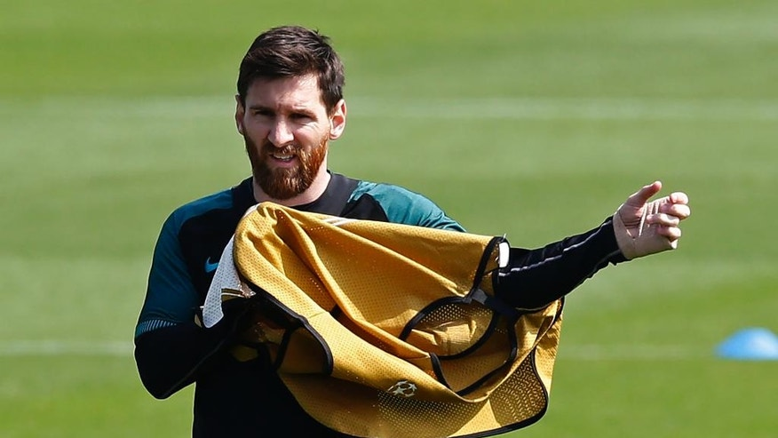 FC Barcelona's Lionel Messi put on his bib during a training session at the Sports Center FC Barcelona Joan Gamper in Sant Joan Despi, Spain, Tuesday, April 18, 2017. FC Barcelona will play against Juventus in a Champions League quarterfinal, second-leg soccer match on Wednesday .(AP Photo/Manu Fernandez)