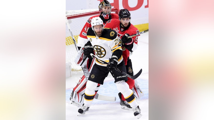 FILE - In this April 15, 2017, file photo, Boston Bruins center Dominic Moore (28) tries to screen Ottawa Senators goalie Craig Anderson (41) as Ottawa Senators center Derick Brassard (19) defends during first period of Game 2 NHL Stanley Cup hockey playoff action in Ottawa. Teams are using the art of the screen for an edge this postseason. (Sean Kilpatrick/The Canadian Press via AP, File)
