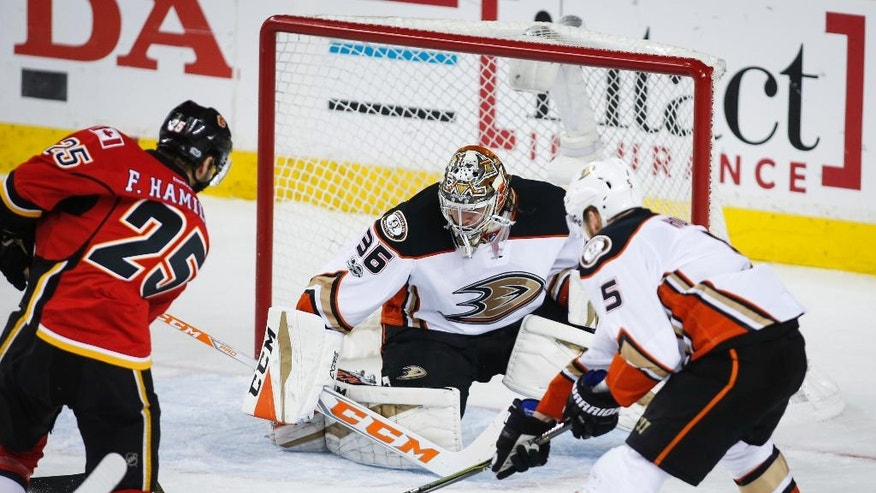 Anaheim Ducks goalie John Gibson, center, watches as teammate Korbinian Holzer, right, of Germany, poke-checks Calgary Flames' Freddie Hamilton during the second period of Game 4 in a first-round NHL hockey Stanley Cup playoff series Wednesday, April 19, 2017, in Calgary, Alberta. (Jeff McIntosh/The Canadian Press via AP)