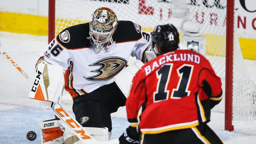 Anaheim Ducks goalie John Gibson, left, deflects a shot from Calgary Flames' Mikael Backlund, of Sweden, during the second period of Game 4 in a first-round NHL hockey Stanley Cup playoff series Wednesday, April 19, 2017, in Calgary, Alberta. (Jeff McIntosh/The Canadian Press via AP)