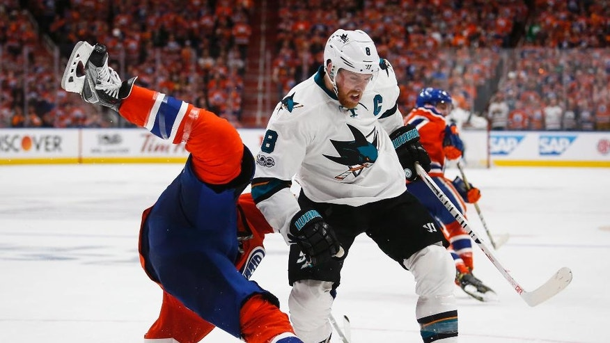San Jose Sharks' Joe Pavelski, right, upends Edmonton Oilers' Milan Lucic during the third period of Game 5 of a first-round NHL hockey Stanley Cup playoff series, Thursday, April 20, 2017, in Edmonton, Alberta. (Jeff McIntosh/The Canadian Press via AP)