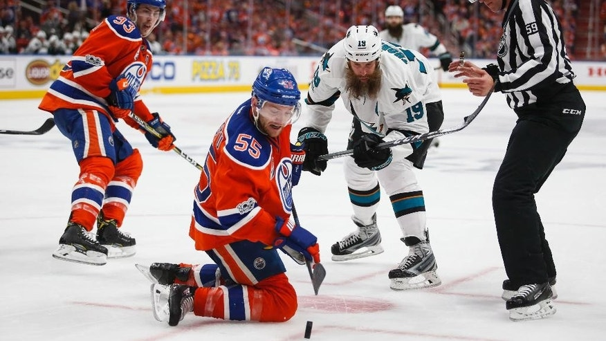 San Jose Sharks' Joe Thornton, center right, looks on as Edmonton Oilers' Mark Letestu, center left, plays the puck from his knees during the third period of Game 5 of a first-round NHL hockey Stanley Cup playoff series, Thursday, April 20, 2017, in Edmonton, Alberta. (Jeff McIntosh/The Canadian Press via AP)