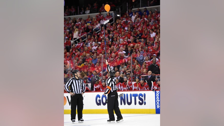 Referee Wes McCauley (4) reaches for a balloon above the ice during the first period of Game 5 in an NHL Stanley Cup hockey first-round playoff series between the Washington Capitals and the Toronto Maple Leafs, Friday, April 21, 2017, in Washington. (AP Photo/Nick Wass)