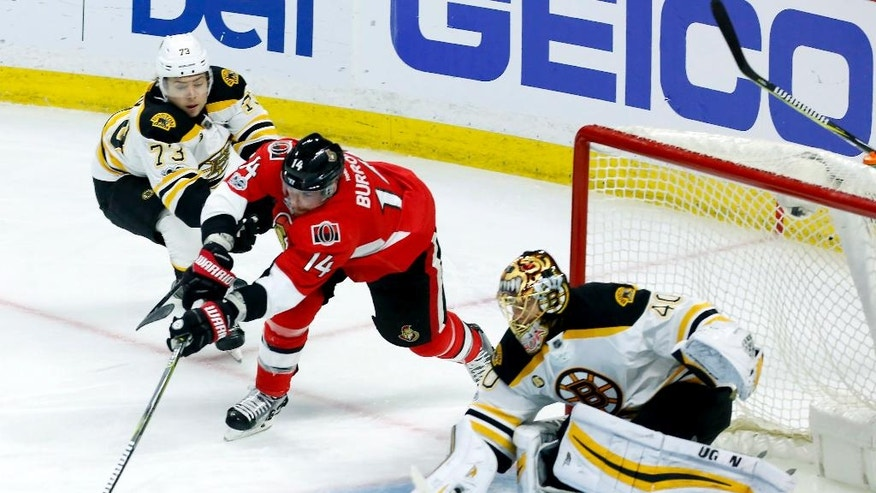 Ottawa Senators left wing Alex Burrows (14) tries the wraparound on Boston Bruins goalie Tuukka Rask (40) as Bruins' Charlie McAvoy (73) defends during the third period of Game 5 of a first-round NHL hockey Stanley Cup playoff series, Friday, April 21, 2017, in Ottawa, Ontario. (Fred Chartrand/The Canadian Press via AP)