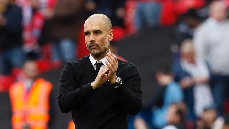 Manchester City manager Pep Guardiola applauds at the end of the English FA Cup semifinal soccer match between Arsenal and Manchester City at Wembley stadium in London, Sunday, April 23, 2017. Arsenal won 2-1. (AP Photo/Kirsty Wigglesworth)