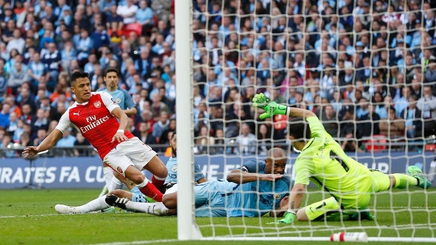 Arsenal's Alexis Sanchez, left, scores his side's second goal past Manchester City goalkeeper Claudio Bravo, right, during the English FA Cup semifinal soccer match between Arsenal and Manchester City at Wembley stadium in London, Sunday, April 23, 2017. (AP Photo/Kirsty Wigglesworth)