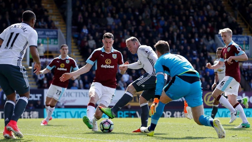 Manchester United's Wayne Rooney, centre right, in action to score his side's second goal of the game against Burnely, with Wayne Rooney, right, during their English Premier League soccer match at Turf Moor in Burnley, England, Sunday April 23, 2017. (Martin Rickett/PA via AP)