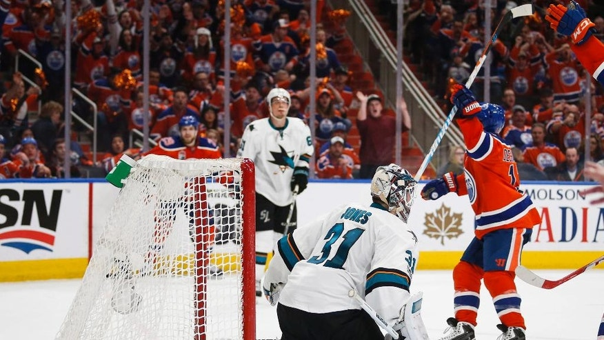 San Jose Sharks goalie Martin Jones kneels on the ice as Edmonton Oilers' David Desharnais celebrates his game-winning goal during overtime of Game 5 of a first-round NHL hockey Stanley Cup playoff series, Thursday, April 20, 2017, in Edmonton, Alberta. The Oilers won 4-3. (Jeff McIntosh/The Canadian Press via AP)