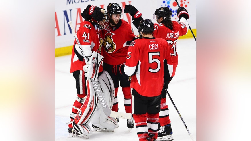 Ottawa Senators goalie Craig Anderson (41) celebrates with Derick Brassard (19), Cody Ceci (5) and Erik Karlsson (65) after the Senators defeated the New York Rangers 2-1 during Game 1 of an NHL hockey second-round playoff series, Thursday, April 27, 2017, in Ottawa, Ontario. (Sean Kilpatrick/The Canadian Press via AP)