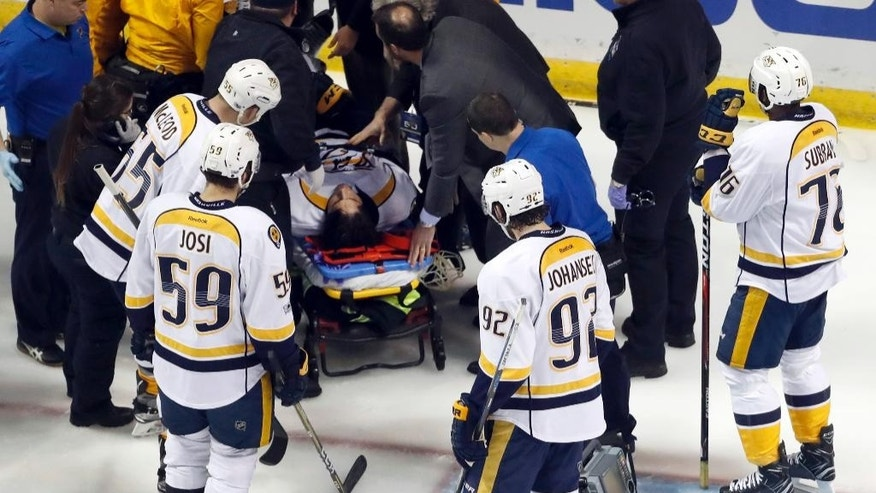 Teammates watch as Nashville Predators' Kevin Fiala, of Switzerland, is taken off on a stretcher during the second period in Game 1 of an NHL hockey second-round playoff series against the St. Louis Blues Wednesday, April 26, 2017, in St. Louis. (AP Photo/Jeff Roberson)