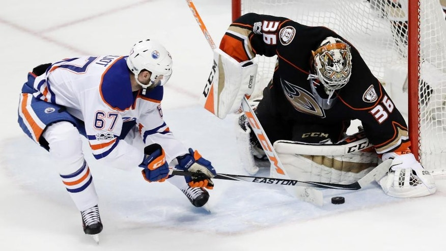 Anaheim Ducks goalie John Gibson, right, blocks a shot by Edmonton Oilers left wing Benoit Pouliot during the second period in Game 2 of a second-round NHL hockey Stanley Cup playoff series in Anaheim, Calif., Friday, April 28, 2017. The Oilers won 5-3. (AP Photo/Chris Carlson)