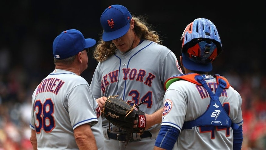 WASHINGTON, DC - APRIL 30: Starting pitcher Noah Syndergaard #34 of the New York Mets talks to coach Dan Warthen #38 and catcher Rene Rivera #44 in the first inning against the Washington Nationals at Nationals Park on April 30, 2017 in Washington, DC. (Photo by Patrick Smith/Getty Images)